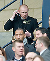 :: CELTIC MANAGER NEIL LENNON PUTS ON A WALKIE TALKIE AS HE TAKES HIS SEAT IN THE STAND  ::