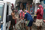 Daily wage laborer cleans themseoves at a tap on a street in burrabazzar in Kolkata.  Whole sale market reopened in Kolkata few days back midst 21 days lock down in India due to covid 19 pandemic. Kolkata, West Bengal, India. Arindam Mukherjee.