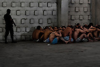 """Mara gang members, having hands behind theirs heads and sitting on the floor, pass through a random search at the detention center in San Salvador, El Salvador, 20 February 2014. Although the country's two major gangs reached a truce in 2012, the police holding cells currently house more than 3000 inmates, five times more than the official built capacity. Partly because the ordinary Mara gang members did not break with their criminal activities (extortion, street-level distribution of drugs, etc.), partly because Salvadorean police still applies controversial anti-gang law which allows to detain almost anyone for """"suspicion of gang membership"""". Accused young men are held in police detention centers where up to 25 inmates may share a cell of five-by-five metres. Here, in the dark overcrowded cages, under harsh and life-threatening conditions, suspected gang members wait long months, sometimes years, for trial or for to be transported to a regular prison."""