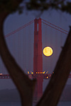 The February full moon sets behind the Golden Gate Bridge as seen from St. Francis Yacht Club, San Francisco, CA.