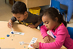 Education preschool 3-4 year olds art activity boy and girl side by side gluing small glitter and sequin items on bookmarks
