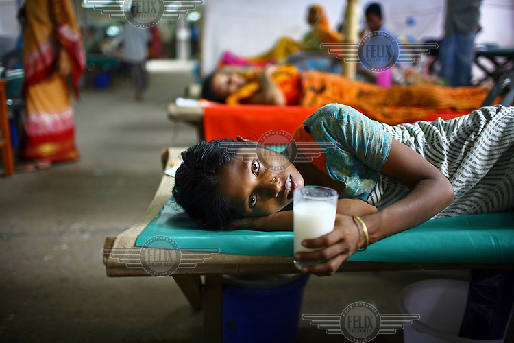 A patient lies on a bed holding a drink while receiving treatment for diarrhoea, at the International Centre for Diarrhoea Disease Research, Bangladesh (ICDDR B). The ICDDR is an international health research organization established in 1978 and credited with discovering oral dehydration therapy for the treatment of diarrhoea and cholera.