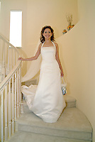 A bride descending stairs in her white wedding dress on the way to her wedding.