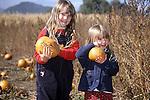 TWO CHILDREN WITH PUMPKINS AT PUMPKIN PATCH EVENT