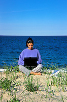 Woman working on a laptop computer while at the beach.