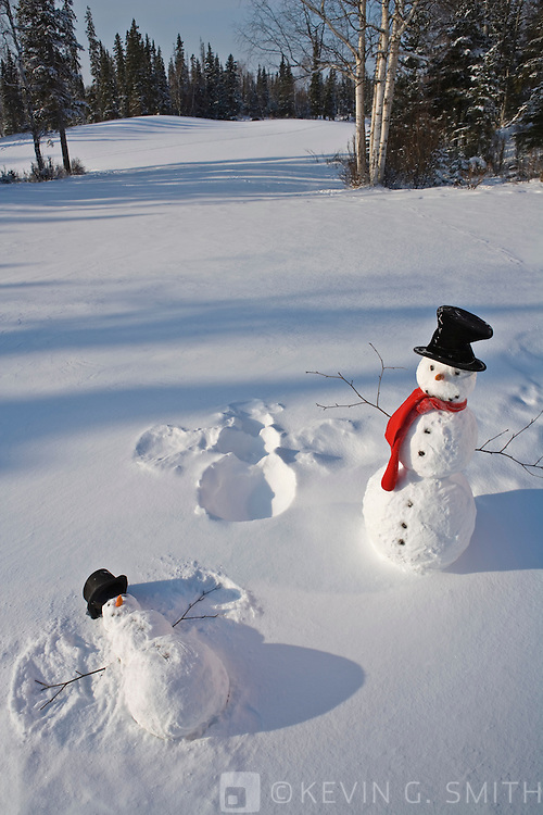 Snowman with red scarf and black top hat standing next baby snowman making snow angel,  snowy meadow, birch trees and spruce forest in back ground.