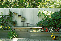 Unique fountain build along wall on deck with pool and planters