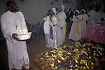 """The Celestial Church of Christ. A baby naming ceremony. The child is being held by a 'spirit medium', as members of the congregation dance around the huge pile of fruit. She will after this ceremony see into the child's future speaking in tongues, the father records hers words while a scribe translates them. 1990s London UK This west African church was founded by S B J Oshoffa Mainly attended by Yoruba people from western Nigeria the church  flourishes with offshoots in London Paris and New York This  photograph is taken from the book The Storm is Passing Over"""""""