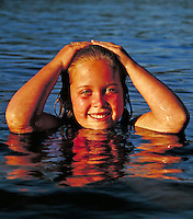 girl with arms up and hands on head poking out of water showing her reflection in water.