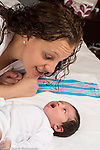 10 day old newborn baby girl alert on back interacting with mother gazing at her