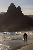 Rio de Janeiro, Brazil. Dois Irmaos (Two Brothers) mountain with a couple arm in arm walking at the edge of the water.
