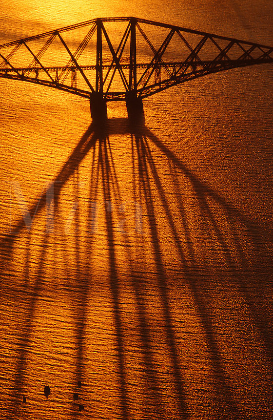 .Aerial shot of the Forth Rail Bridge, Edinburgh, Scotland, seen against a shining golden sea...Keywords: bridge, railway, railroad, cantilever, steel, sea, shining, sunset, Forth, Edinburgh, Scotland, estuary