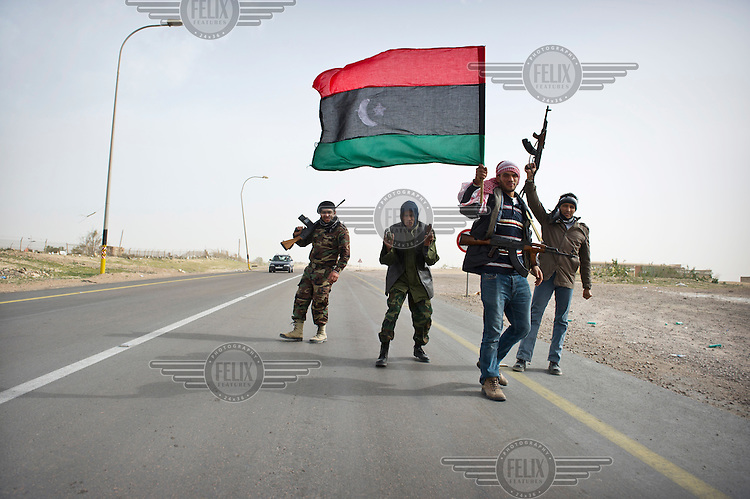 Rebel fighters in Brega show off their weapons and wave a pre-Gaddafi Libyan flag. On 17 February 2011 Libya saw the beginnings of a revolution against the 41 year regime of Col Muammar Gaddafi.