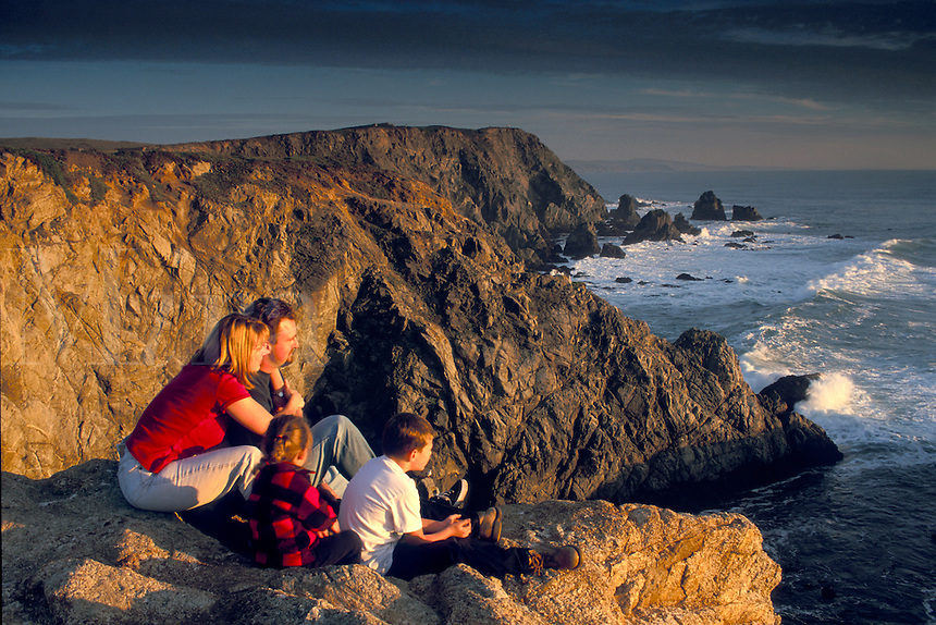 Family watching the sunset from coastal cliffs above the Pacific Ocean at Bodega Head, Sonoma Coast California.