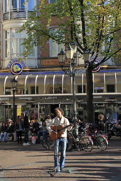 Musician playing guitar at Dam Square, Amsterdam, Netherlands