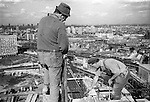 Irish navvies navvie navvy labourers construction workers at the top of and working on a Nine Elms tower block. Vauxhaul Cross below them. South London skyline looking east. 1974