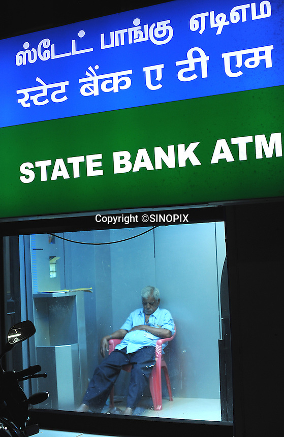 Grey haired guard man is having a nap behind the sign of ATM at State Bank in Madras, India