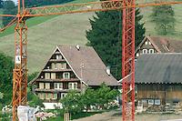 Switzerland. Zoug. A modern construction near old traditionnal wooden chalets. © 1989 Didier Ruef