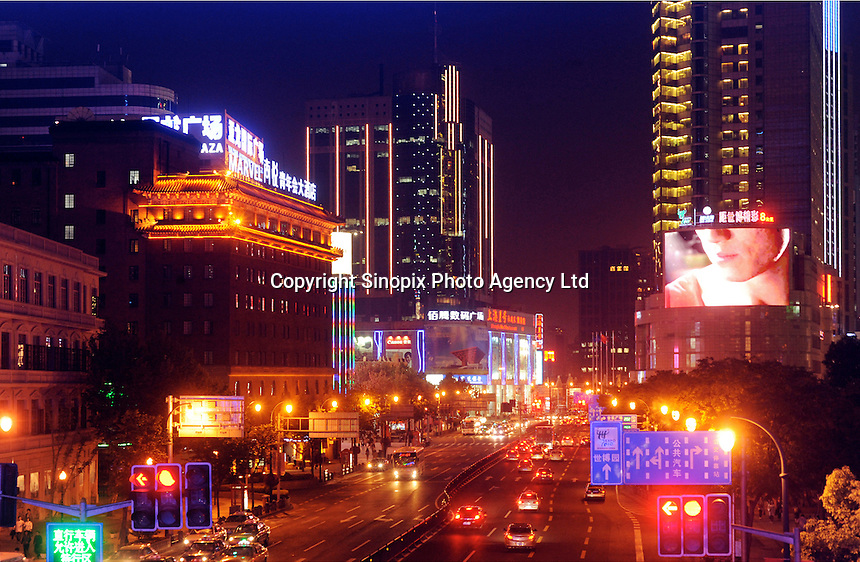 Automobiles are seen on the lanes, a roadsign ......indicates the direction to Shanghai World Expo., many hotels and luxury malls are located in the downtown area of Shanghai, China..
