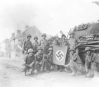 """Lined up in front of a wrecked German tank and displaying a captured swastika, is group of Yank infantrymen who were left behind to """"mop-up"""" in Chambois, France, last stronghold of the Nazis in the Falaise Gap area.  August 20, 1944. Tomko.  (Army Surgeon General)<br /> NARA FILE #:  112-SGA-44-12123<br /> WAR & CONFLICT BOOK #:  1049"""