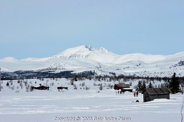 Storrondan in Rondane National Park in the background, skiiers enjoying the beautyfull Norwegian winters day