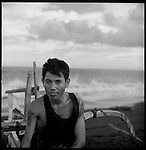 A fisherman relaxes while sitting on his outrigger canoe.