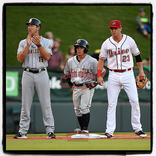 "Third baseman Jose Carrera (1) of the Charleston RiverDogs stands on third base between manager Patrick Osborn (13) and Bobby Dalbec (23) of the Greenville Drive in Game 2 of the South Atlantic League Southern Division Playoff on Friday, September 8, 2017, at Fluor Field at the West End in Greenville, South Carolina. Charleston won, 2-1, and the series is tied at one game each. Carrera is listed in the roster at 5'2"". (Tom Priddy/Four Seam Images)"