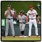 """Third baseman Jose Carrera (1) of the Charleston RiverDogs stands on third base between manager Patrick Osborn (13) and Bobby Dalbec (23) of the Greenville Drive in Game 2 of the South Atlantic League Southern Division Playoff on Friday, September 8, 2017, at Fluor Field at the West End in Greenville, South Carolina. Charleston won, 2-1, and the series is tied at one game each. Carrera is listed in the roster at 5'2"""". (Tom Priddy/Four Seam Images)"""