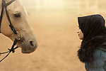 A trust look between a woman and her white horse. Photo by Sanad Ltefa