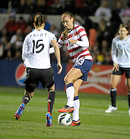 US forward Alex Morgan (13) makes a back heel pass in front of Germany's Verena Faibt (15).  The U.S. Women's National Team tied Germany 1-1 in a friendly at Toyota Park in Bridgeview, IL on October 20, 2012.