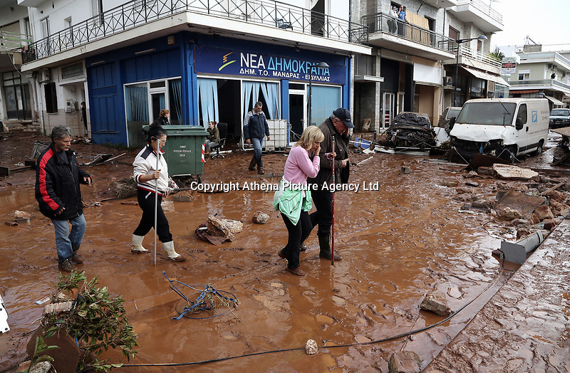Pictured: Locals walk through mud and debris.<br />Re: Five people have reportedly died and severe damage caused by heavy rain and flash flooding in the area of Mandra, near Athens, Greece. Wednesday 15 November 2017