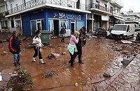 Pictured: Locals walk through mud and debris.<br />