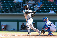 Salt River Rafters right fielder Monte Harrison (4), of the Miami Marlins organization, follows through on his swing in front of catcher Jhonny Pereda (6) during an Arizona Fall League game against the Mesa Solar Sox at Sloan Park on October 30, 2018 in Mesa, Arizona. Salt River defeated Mesa 14-4 . (Zachary Lucy/Four Seam Images)