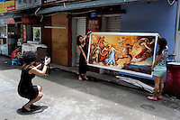 A woman takes a picture of a newly made replica of a work by one of the Great Masters. Dafen is home to an art industry producing replicas, as well as original works, of pieces by the world's great artists for sale overseas. The success of this business has attracted more and more trained artists to the town seeking an opportunity to make a living.