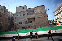 SYRIA, 02.2012, Idlib, Idlib province. © Timo Vogt/EST&OST. People in the street in front of a huge graffito showing the flag of the revolution.