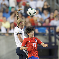 USWNT defender Becky Sauerbrunn  (4) and Korea Republic forward Yoo Younga (12) battle for head ball.  In an international friendly, the U.S. Women's National Team (USWNT) (white/blue) defeated Korea Republic (South Korea) (red/blue), 4-1, at Gillette Stadium on June 15, 2013.