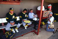 TEMPE, AZ - Pitching coach Dave Duncan and manager Tony La Russa of the Oakland Athletics sit in the dugout with writer George Will before a spring training game against the Seattle Mariners at Tempe Diablo Stadium in Tempe, Arizona in 1991 as they are photographed by Marin Independent Journal photographer Scott Henry. Photo by Brad Mangin