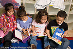 Preschool Headstart 3-5 year olds group of children boy and girls sitting and talking looking at picture books horizontal