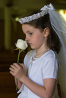 A young girl stands with a rose after her first communion sacrament at a Catholic church in Johnstown, OH.<br />