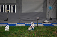 Switzerland. Canton Ticino. Tenero. Camping Campofelice. Gnomes' decoration on a lawn by a caravan. A caravan, travel trailer, camper or camper trailer is towed behind a road vehicle to provide a place to sleep which is more comfortable and protected than a tent. It provides the means for people to have their own home on a journey or a vacation. Campers are restricted to designated sites for which fees are payable. A gnome is a diminutive spirit in Renaissance magic and alchemy, later adopted by more recent authors including those of modern fantasy literature. Its characteristics have been reinterpreted to suit the needs of various story tellers, but it is typically said to be a small humanoid that lives underground. 21.07.2018 © 2018 Didier Ruef
