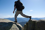 A hiker on the summit of Mount Lincoln heading north on the Franconia Ridge Trail (Appalachian Trail) during the spring months in the White Mountains of New Hampshire USA.