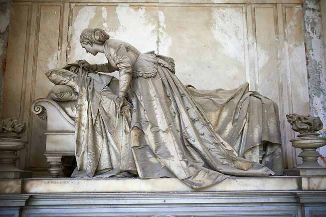 Picture of the stone sculpture of a widow covering the face of a lying corpse sculpted in a Borgeoise realistic style. Section D no 2, the monumental tombs of the Staglieno Monumental Cemetery, Genoa, Italy