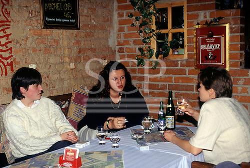 Ostrava, Czech Republic. Three women having a drink in a restaurant, one smoking.