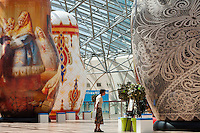 Moscow, Russia, 15/06/2011..A woman inspects an exhibition of of giant Russian matryoshki, or nesting dolls, in the newly-opened Afimall shopping centre. The dolls, designed by Boris Krasnov, are from 6 to 13 metres high, and each is decorated in a different style of traditional Russian folk art..Left - right: Fedoskono, Russian Imperial porcelain, and Vologodskoe lacework styles.