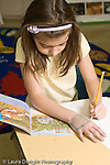 Education Elementary Public Grade 2 science class girl drawing with pencil open book next to her paper vertical