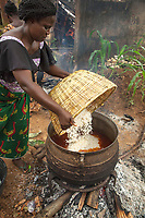 Nigeria. Enugu State. Agbani. Reverend Father Gerald Chukwudi Ani is a catholic priest from the Diocese of Lugano (Ticino, Switzerland). Back in his homeland, he has organized in the family home a party to celebrate his 10th year anniversary of priesthood and the 5th year of his mother's death. A woman is cooking white rice with spicy tomato sauce on a large cauldron on an open fire outdoors. 6.07.19 © 2019 Didier Ruef
