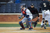 Illinois Fighting Illini catcher Jacob Campbell (9) waits for a throw as Patrick Frick (5) of the Wake Forest Demon Deacons crosses home plate at David F. Couch Ballpark on February 16, 2019 in  Winston-Salem, North Carolina.  The Fighting Illini defeated the Demon Deacons 5-2. (Brian Westerholt/Four Seam Images)