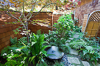 Stepping stone path into small space private secluded Japanese style garden room behind walls of California home
