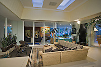 Modern great room with wicker furniture and view of living room in background