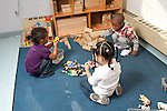 Education preschool first days of school 2-3 year olds two boys and a girl playing separately with toys